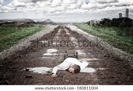 stressed man lying on ground with rain - stock photo