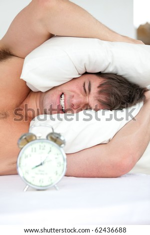 Stressed man woken-up by his alarm clock putting his head under the pillow in the morning