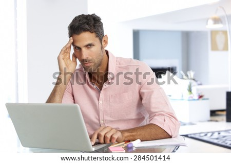 Stressed Man Working At Laptop In Home Office - stock photo