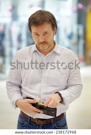 Stressed middle age man holding purse with russian paper money (rubles) at shopping mall - stock photo