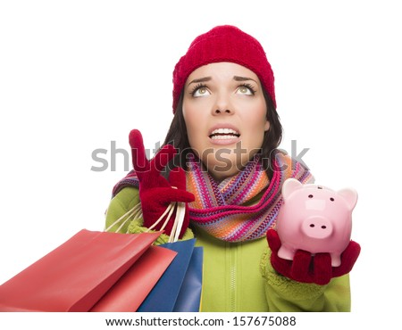 Stressed Mixed Race Woman Wearing Winter Clothing Looking Up Holding Shopping Bags and Piggy Bank Isolated on White Background. - stock photo