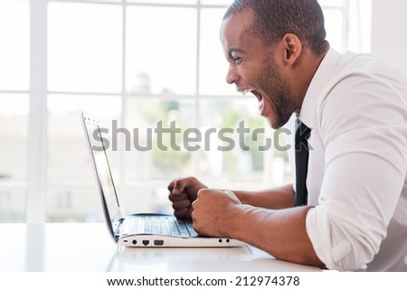 Stressed office worker. Side view of furious young African man in shirt and tie shouting while looking at laptop while sitting at his working place - stock photo