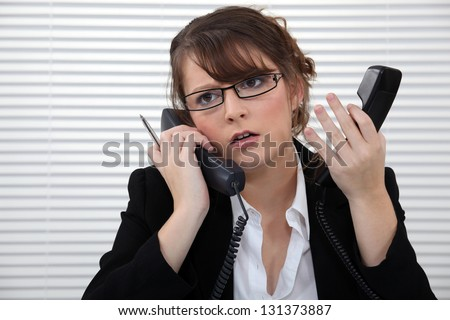 Stressed office worker with two telephones