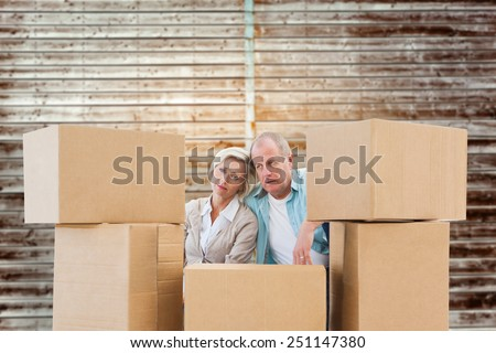 Stressed older couple with moving boxes against wooden planks