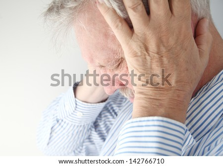 stressed older man holds his head in both hands - stock photo