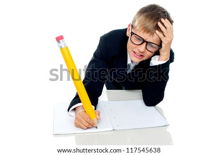 Stressed out boy mid way through his test holding his head in frustration - stock photo