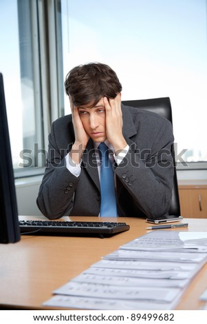 Stressed out businessman sitting at his desk in front of computer