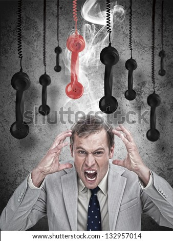 Stressed out businessman with phone receivers hanging down - stock photo