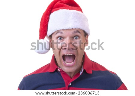 Stressed out Caucasian man wearing red Santa hat screams in disbelief on white background