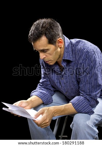 stressed out man reading unpaid bills or taxes - stock photo