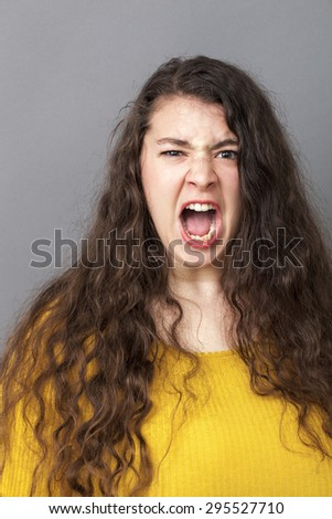 stressed out overweight 20's woman with long brown hair shouting loud for expressing rage and impatience - stock photo