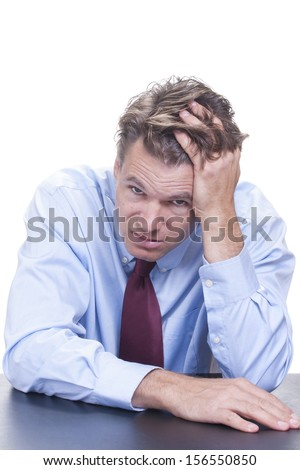 Stressed out white male office worker sits at desk with head leaning into hand and fingers through hair while making face at camera - stock photo