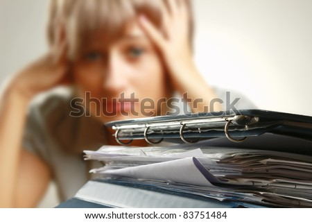 Stressed Out Worker At Her Desk With Files On White Isolated Background - stock photo