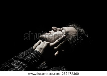 Stressed ,Painful, headache portrait of a young student, man,pointing with finger to his had  trying to remember something or feeling an insupportable pain.Facial expression. - stock photo