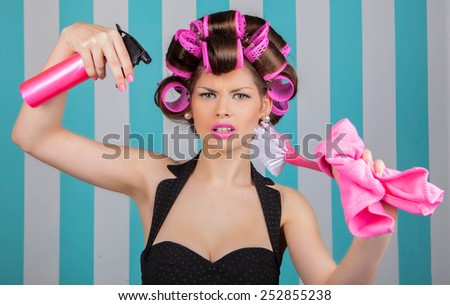stressed retro woman in rollers multitasking spring cleaning - stock photo