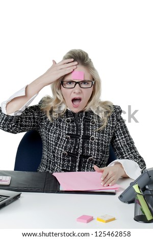 Stressed secretary touching her forehead with pink memo note - stock photo