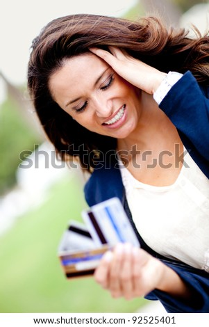 Stressed shopping woman in a financial dilemma holding three credit cards - stock photo