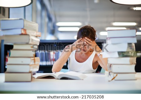 Stressed student of high school sitting at the library desk, tired and bored to study asian student girl preparing to the exams, female student with pile of books study hard for exam in high school - stock photo