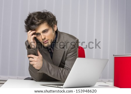 Stressed thoughtful young executive showing an attitude of failure, disappointment with hand at his temple at work. Corporate failure. Banking, insurance, law, sales. - stock photo