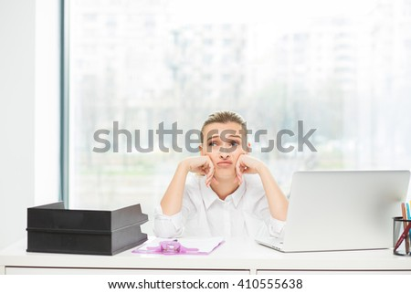 stressed woman behind the desk after a hard day work - stock photo
