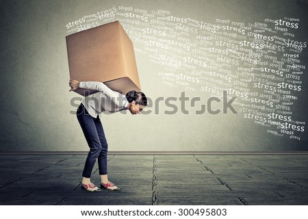 Stressed woman carrying on her back shoulders large box