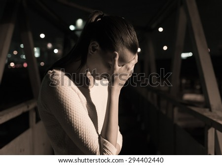 Stressed woman in a night time setting.  - stock photo