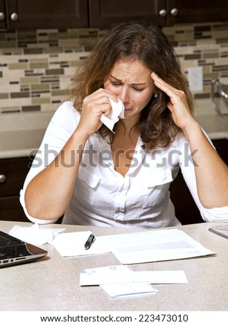 stressed woman looking at bills while sitting in the kitchen  - stock photo