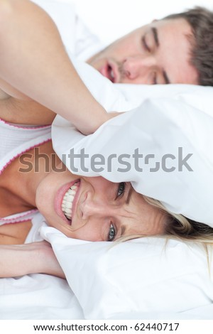 Stressed woman lying on the bed with her boyfriend snoring putting her head under the pillow - stock photo