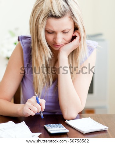 Stressed woman paying her bills in a living-room