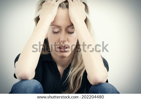 Stressed woman sitting on ground and holding hands to head - stock photo