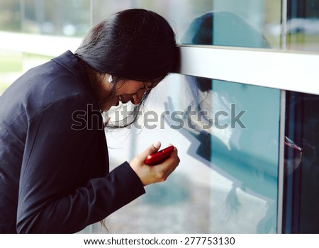 Stressed woman with cellphone near on the office building - stock photo