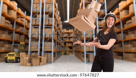 Stressed woman with helmet trying to catch flying parcels in a warehouse