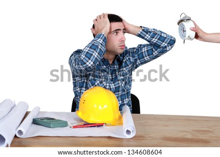 stressed worker looking at a clock - stock photo