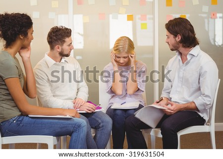 Stressed worker with her colleagues with a headache