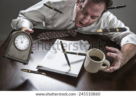 Stressed Yelling Man At Desk With Pens, Coffee, Glasses and Clock Flying Up in the Air. - stock photo