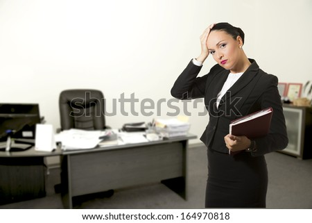 Stressed young business woman,inside her office. - stock photo