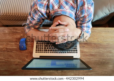 Stressed young businessman covering face with hands at messy desk in office - stock photo