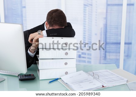 Stressed young businessman resting head on stacked binders at office desk - stock photo