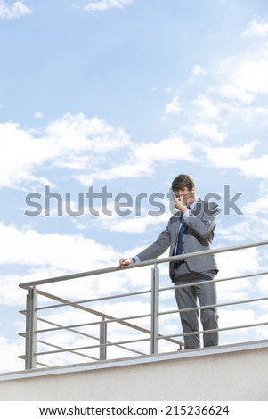 Stressed young businessman rubbing eyes on terrace against sky - stock photo