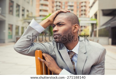 Stressed young businessman sitting outside corporate office. Negative human emotion facial expression feelings. - stock photo