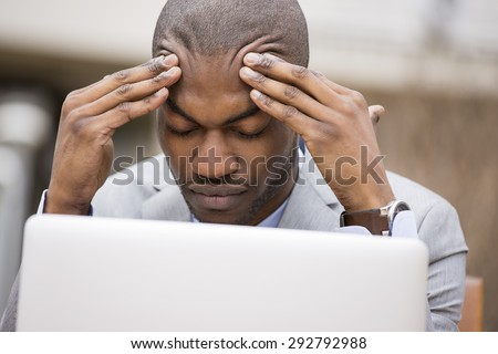 stressed young businessman sitting outside corporate office working on laptop computer holding head with hands looking down. Negative human emotion facial expression feelings. - stock photo
