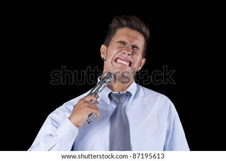 Stressed young businessman with a gun pointing to his head (isolated on black)