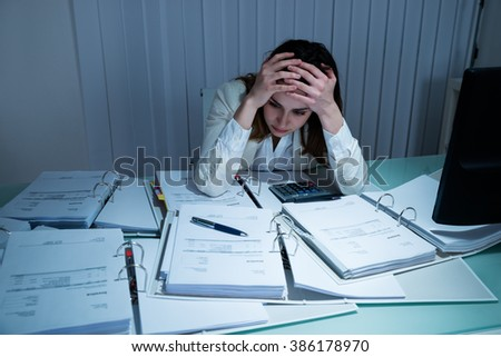 Stressed Young Businesswoman Working Late In Office - stock photo