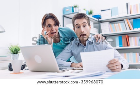 Stressed young couple checking bills, taxes and bank account balance, they are panicking, debt and cost of living concept - stock photo