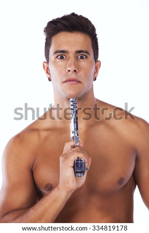 Stressed young man with a gun pointing to his head (isolated on black) - stock photo