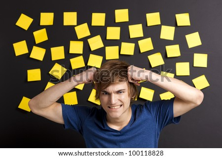 Stressed young student in front of a board full of yellow notes - stock photo