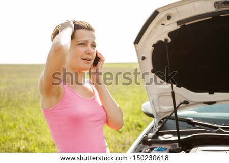 Stressed Young Woman Breakdown With Car Calling For Service On Mobilephone - stock photo