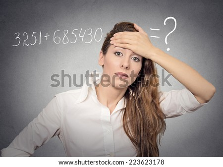 Stressed young woman can't solve math problem on her mind having headache isolated on grey wall background. Human face expressions, emotions, feelings - stock photo