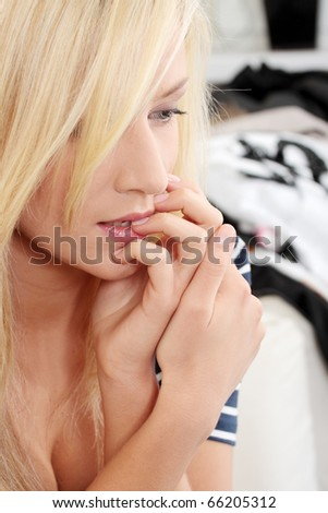 Stressed young woman eating her nails - stock photo