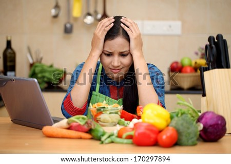 Stressed young woman in kitchen  - stock photo